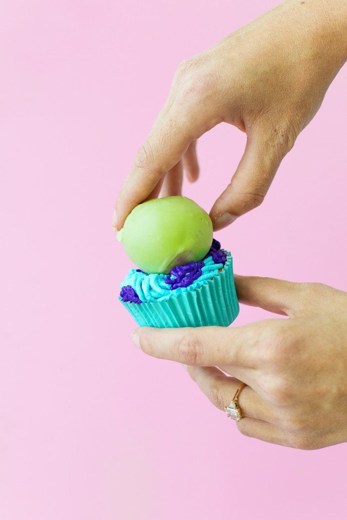 Green cake ball onto of blue and purple frosted Monster cupcake