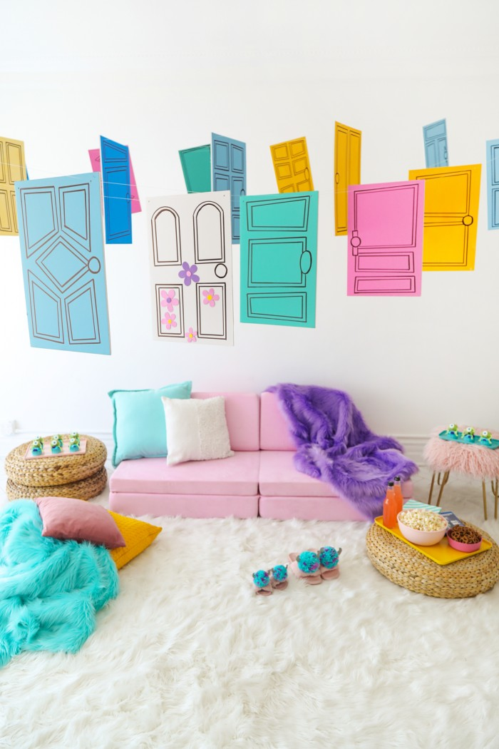 Pink couch with Monster's Inc inspired foam doors hanging above