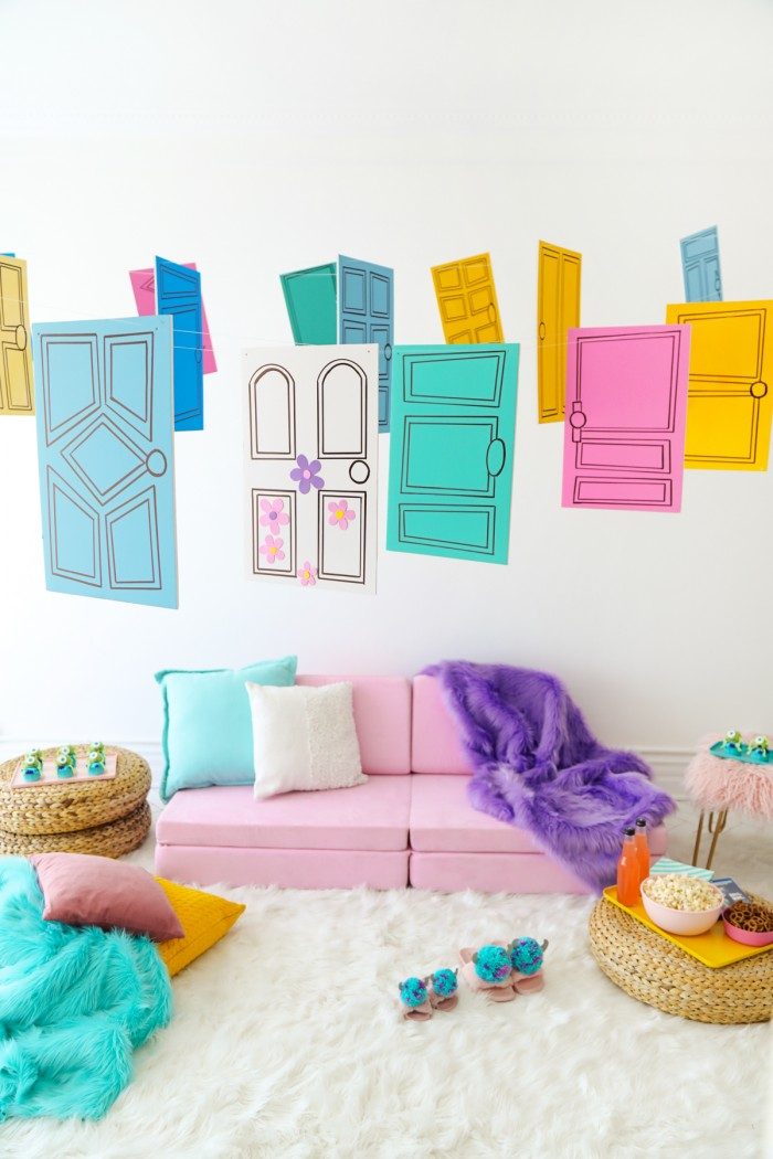 Pink couch with colorful Monster's Inc door decorations hanging above it on a white faux fur rug