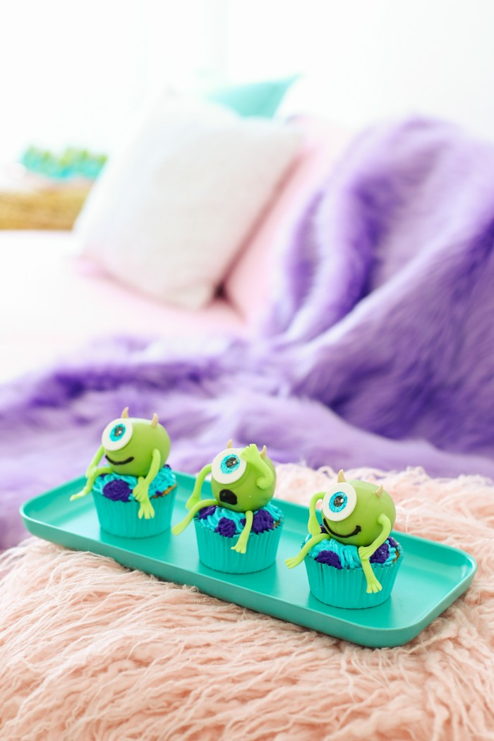 Mike wazowski Monsters Inc cupcakes sitting on a teal tray on a pink faux fur blanket