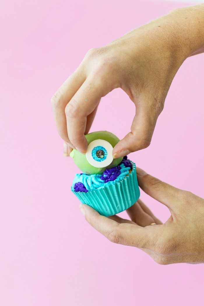 Fondant eye being placed on green cake ball on a cucpake