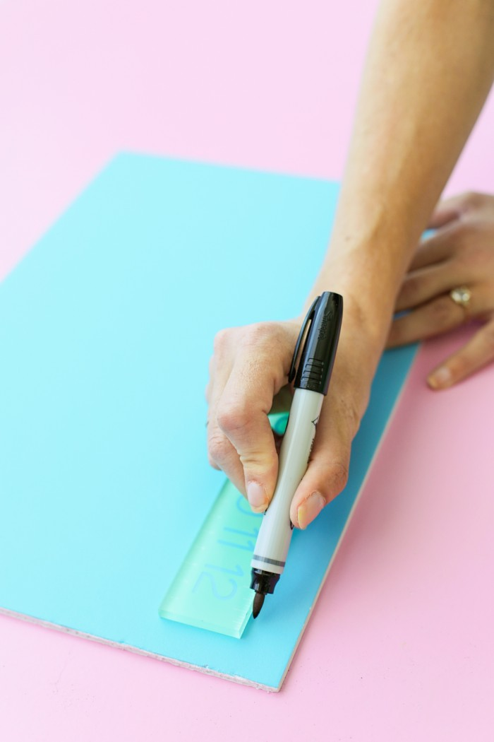 Drawing a line on a foam core door decoration with a black permanent marker