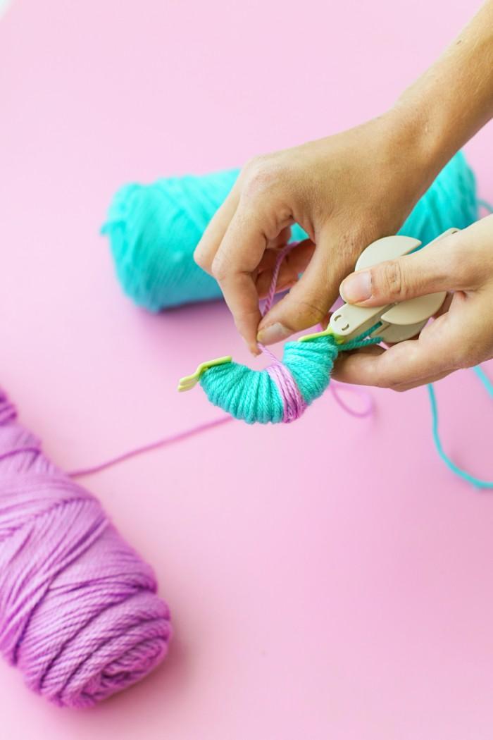 Blue and purple yarn wrapped around a Pom Pom maker
