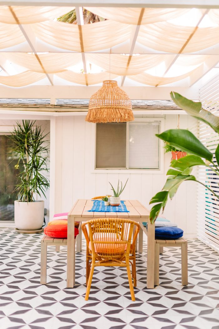 Black and white tile patio with dining table and colorful pillows with a pergola above it