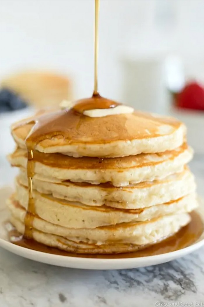 Stack of pancakes with syrup being poured over it