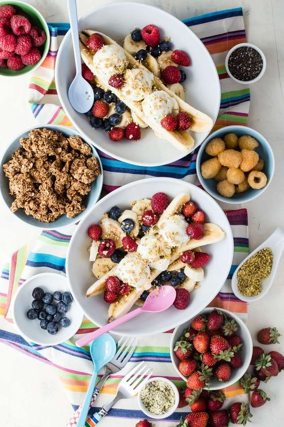 Breakfast Banana Split with bowls of granola and berries on a striped towel