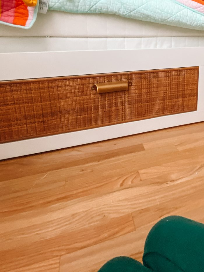 Cane drawer with gold handle on white daybed
