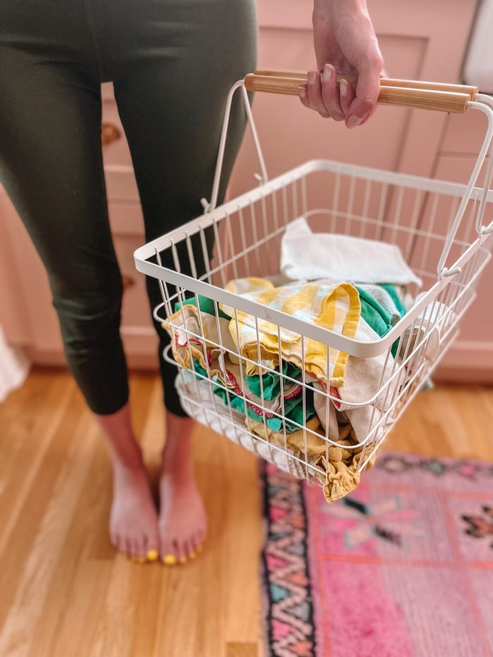 woman holding white metal basket with dirty unpaper towels