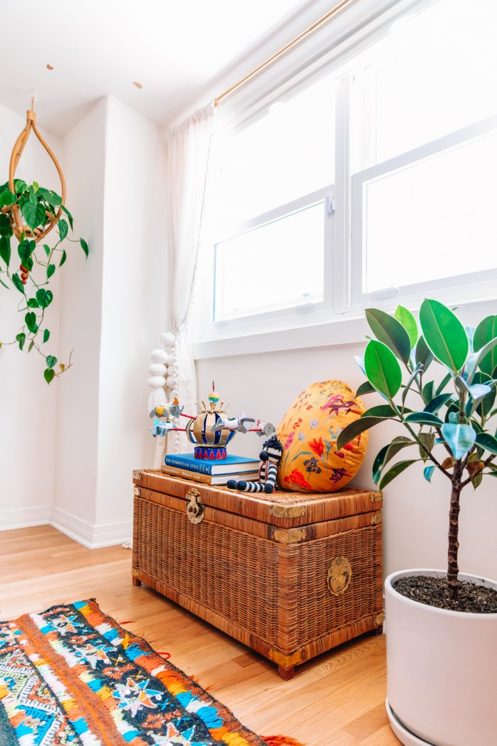 wicker trunk with pillow and books on top under a window next to two plants and a colorful moroccan rug