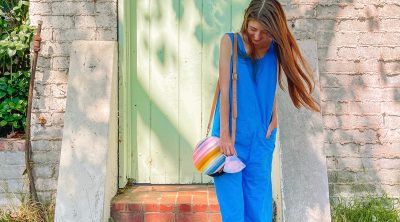 Woman wearing blue jumpsuit with striped purse walking down stairs in front of green gate