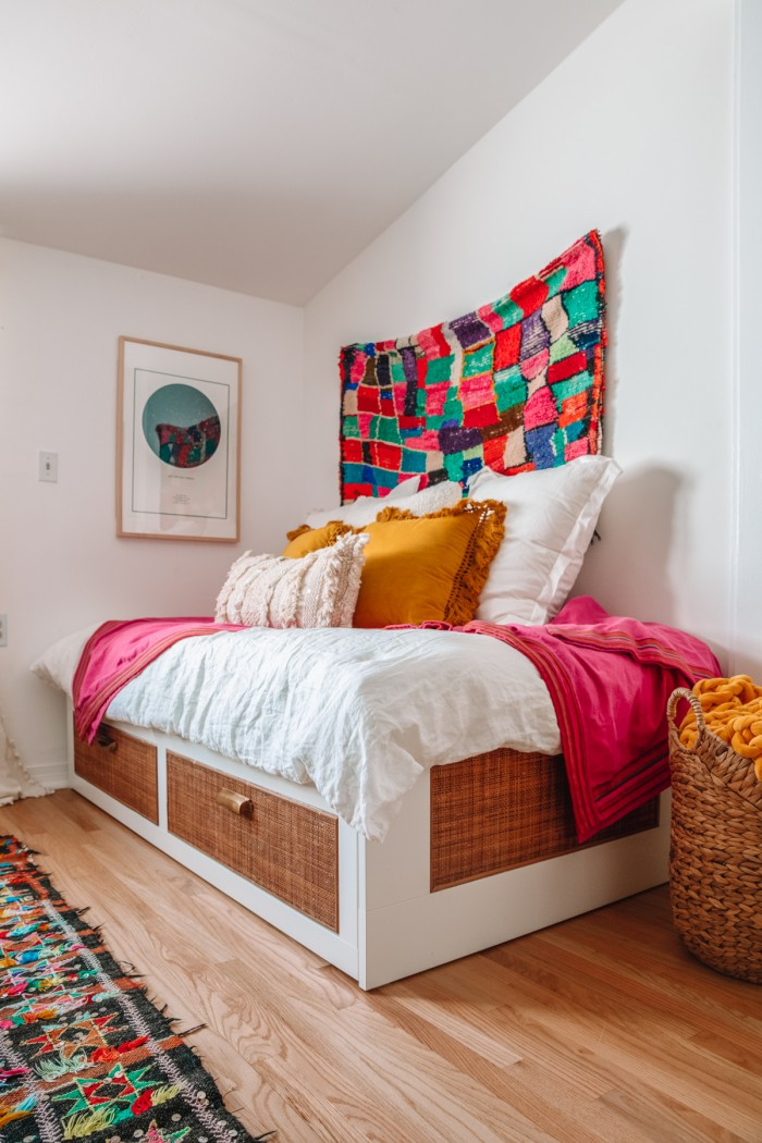 Rattan IKEA daybed with pillows on top and a rug hanging behind it