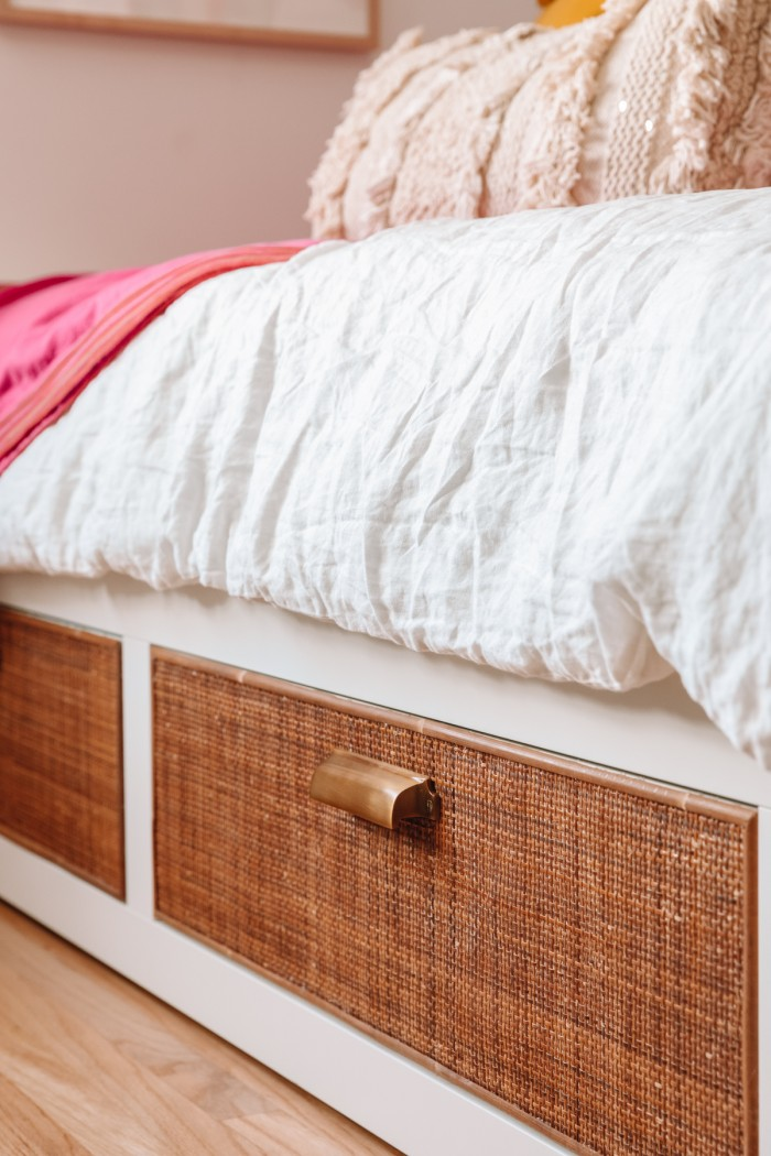 Cane IKEA bed drawer with white linen comforter