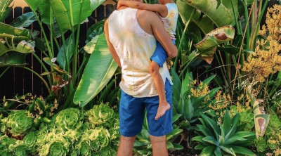 Father and son in tie dye shirts and blue shorts in front of overgrown plants