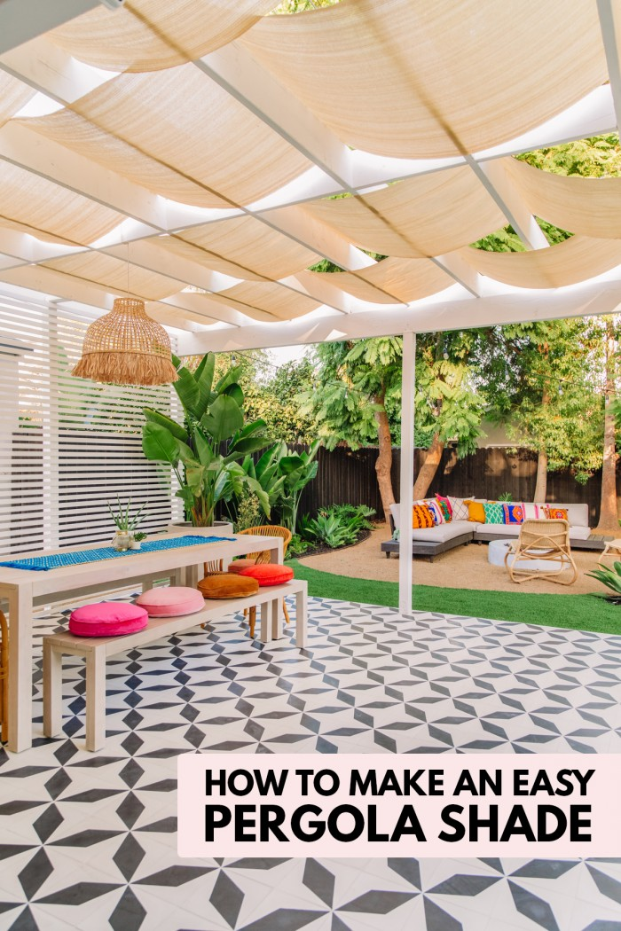 Backyard patio with patterned tile, long table and pergola with shade