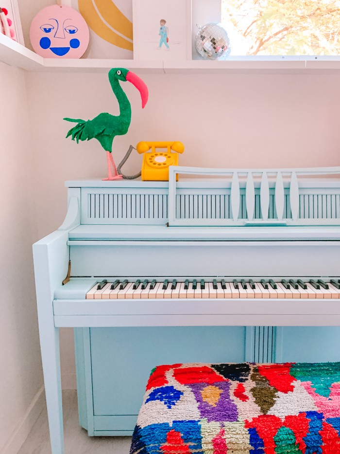 Blue piano in a corner with colorful textile bench and a yellow phone on top