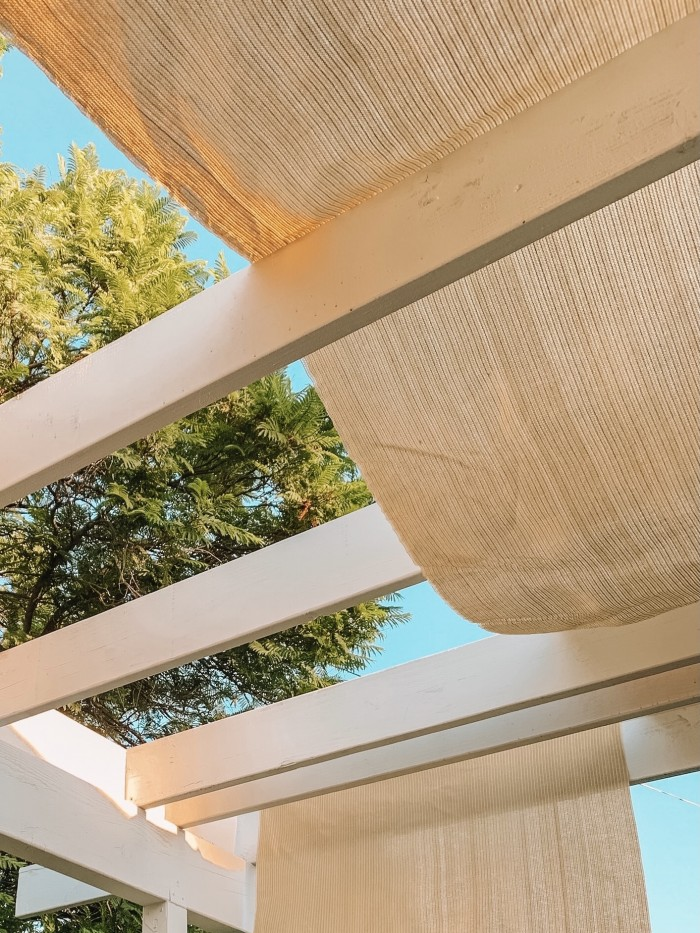 Pergola sun shade hanging on white beams with green tree in background