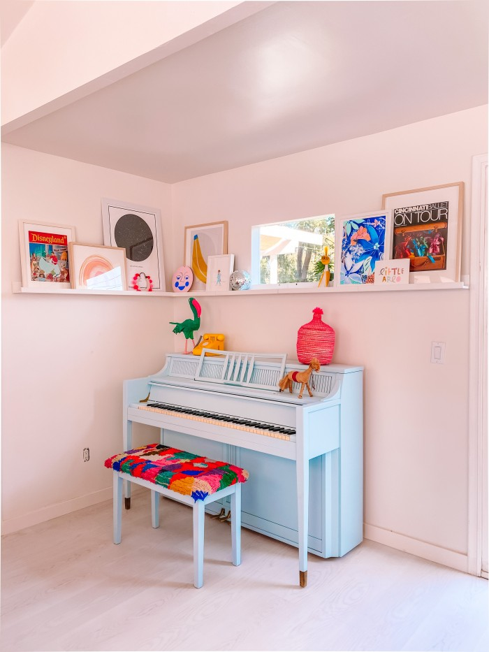 Blue piano in a corner with art on a ledge above and a window