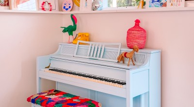 Blue Piano with colorful bench and art ledge behind it