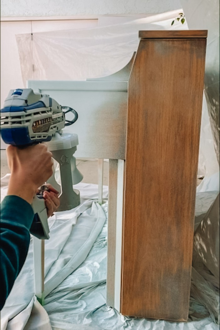 Painting the side of a wood piano with a paint sprayer