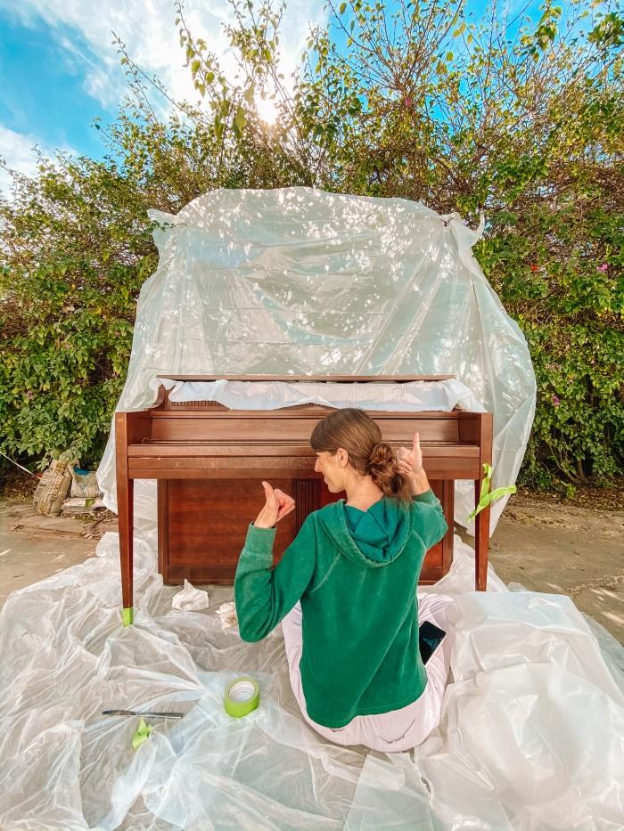 Wood piano in front of plastic tarp