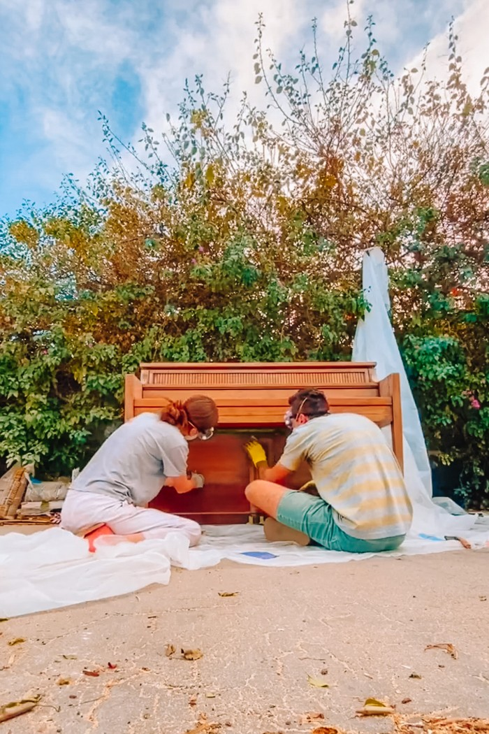 Man and woman sanding a wood piano outside in front of greenery