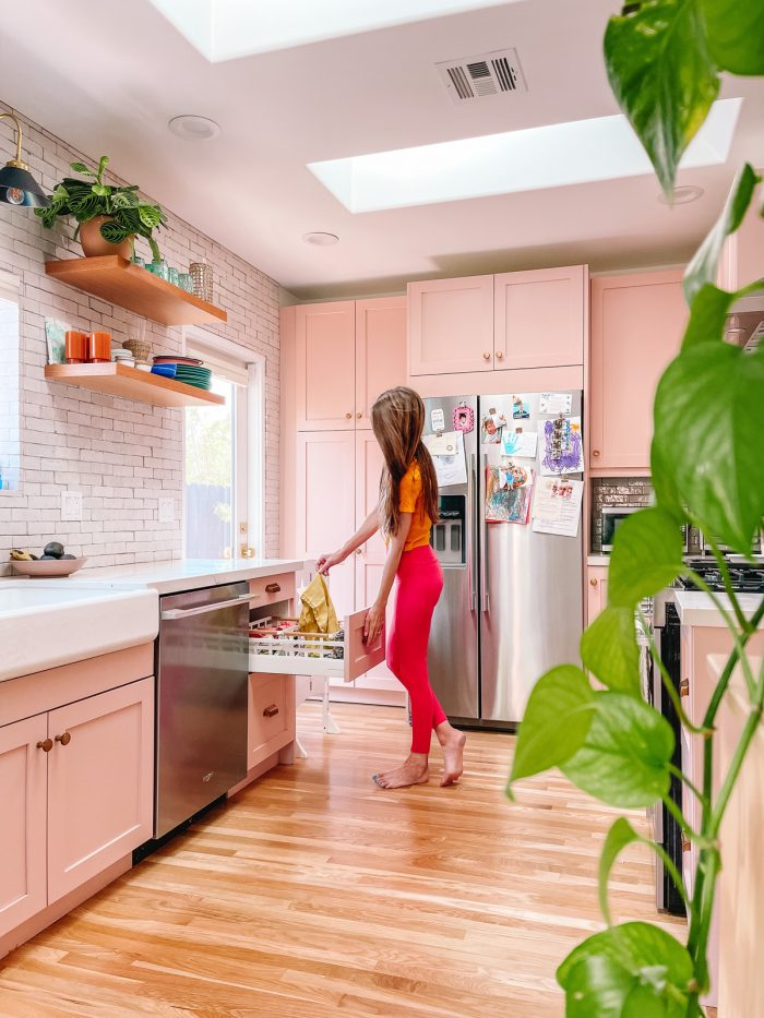Woman in pink kitchen pulling towel out of drawer with a plant in the foreground