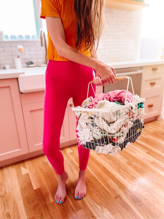 Woman wearing pink leggings holding a white metal basket with rags in it