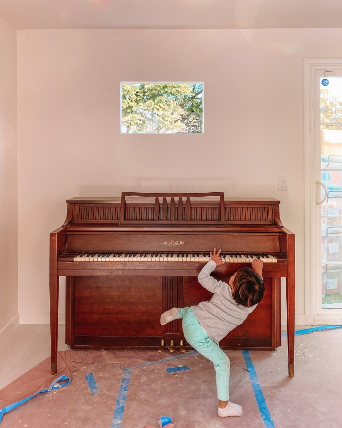 Wood piano with child playing in front of it