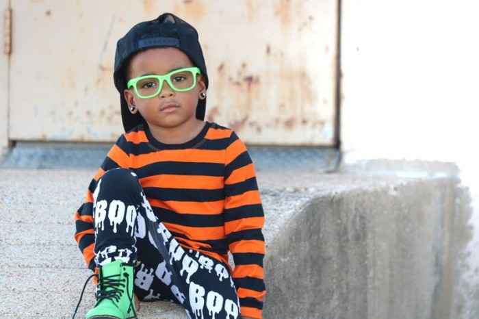 child in green glasses wearing a black and orange stripe shirt sitting on stairs