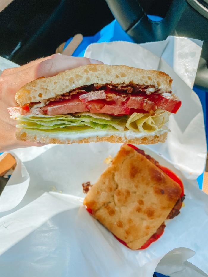 BLT sandwich on white paper on someone's lap