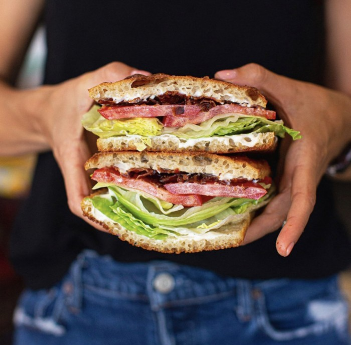 BLT stacked and held in two hands in front of a black shirt