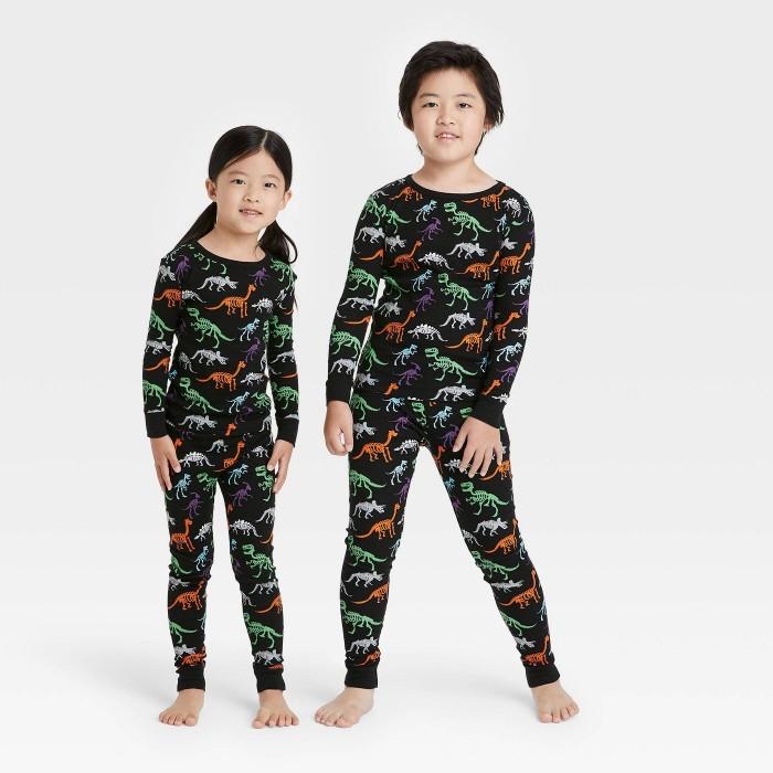Two kids wearing dinosaur skeleton pajamas on a white background