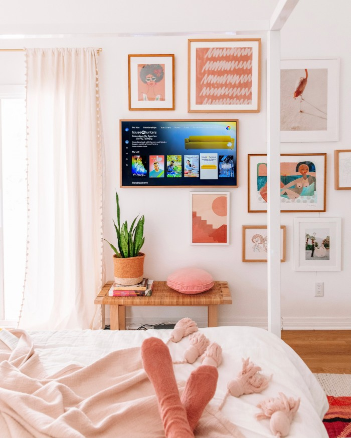 Discovery Plus on TV as a part of a gallery wall with feet in the foreground on a bed