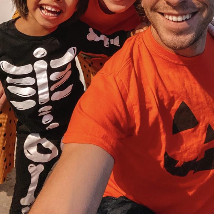 Kid in Halloween Skeleton Pajamas and Dad in Jack-o-Lantern Shirt