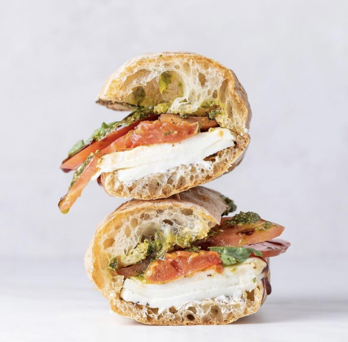 Caprese sandwich stacked on a white background