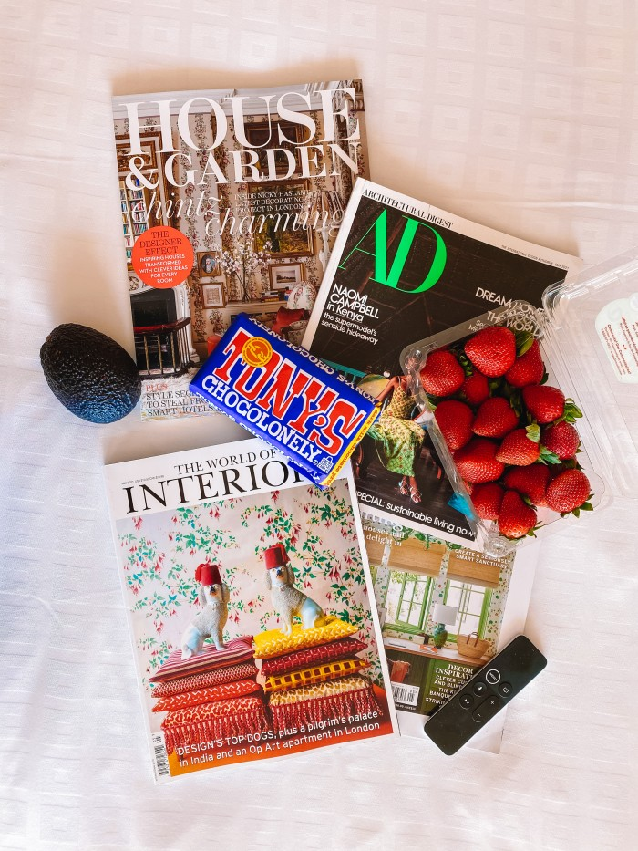 Shelter magazines, strawberries, chocolate bar and avocado laying on a bed