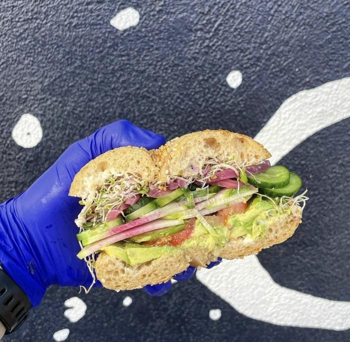 Vegetarian bagel sandwich held by hand in a blue glove