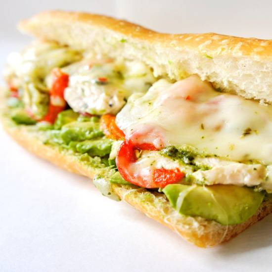 Honey cilantro lime chicken sandwich with avocado on a white background