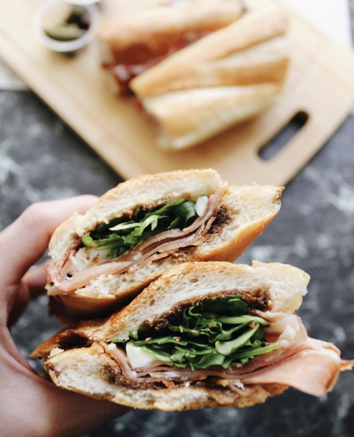 Larchmont Wine and Cheese Proscuitto Sandwich held about a table