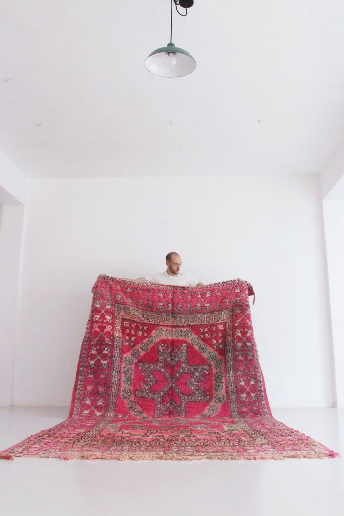 Vintage Fuchsia Moroccan Rug held in front of a white wall