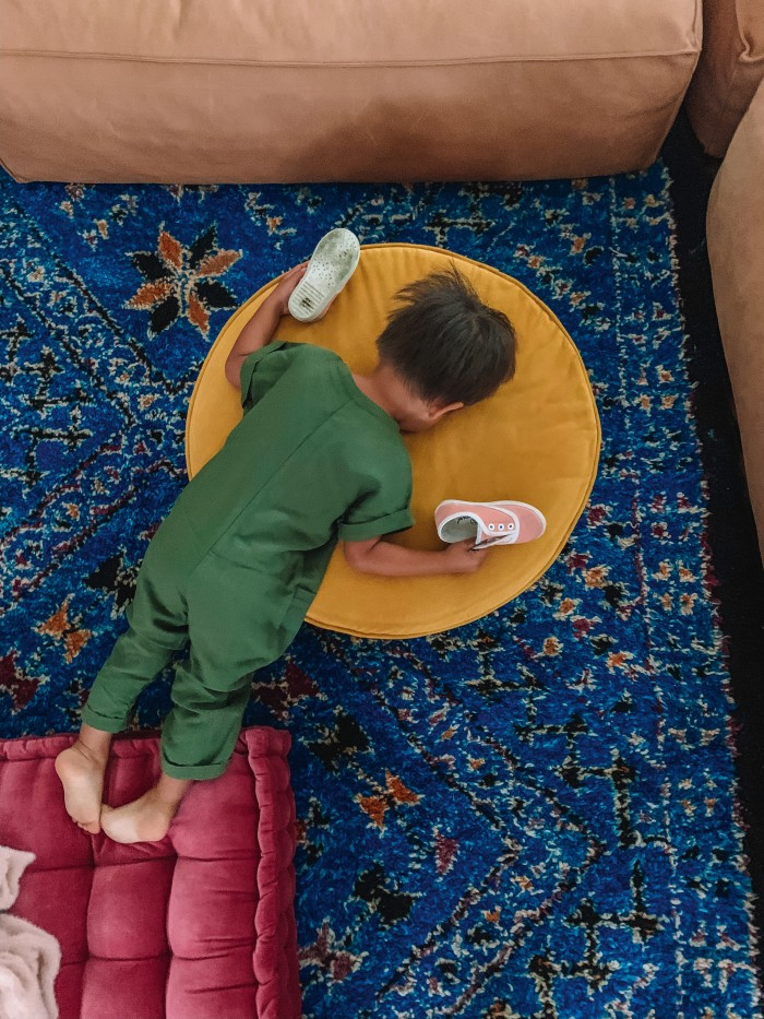 Blue living room rug with child laying on top