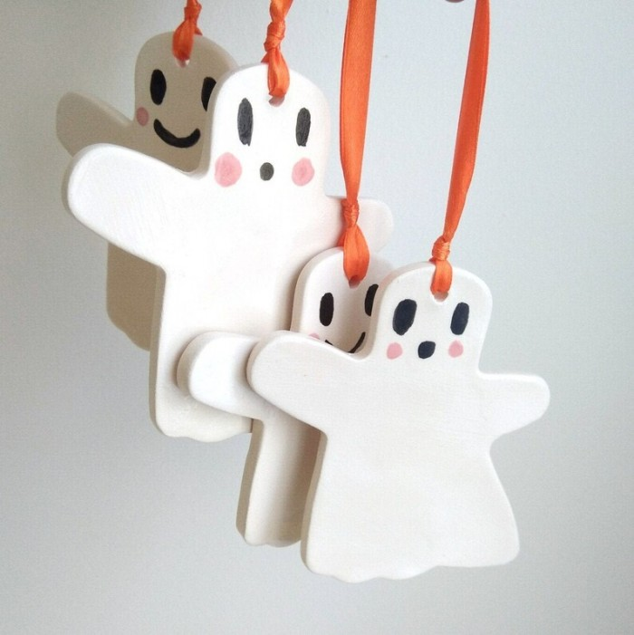ceramic ghost ornaments hanging against a white wall