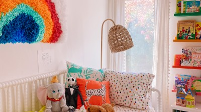 Colorful kids room with bed and rainbow wall hanging above the bed