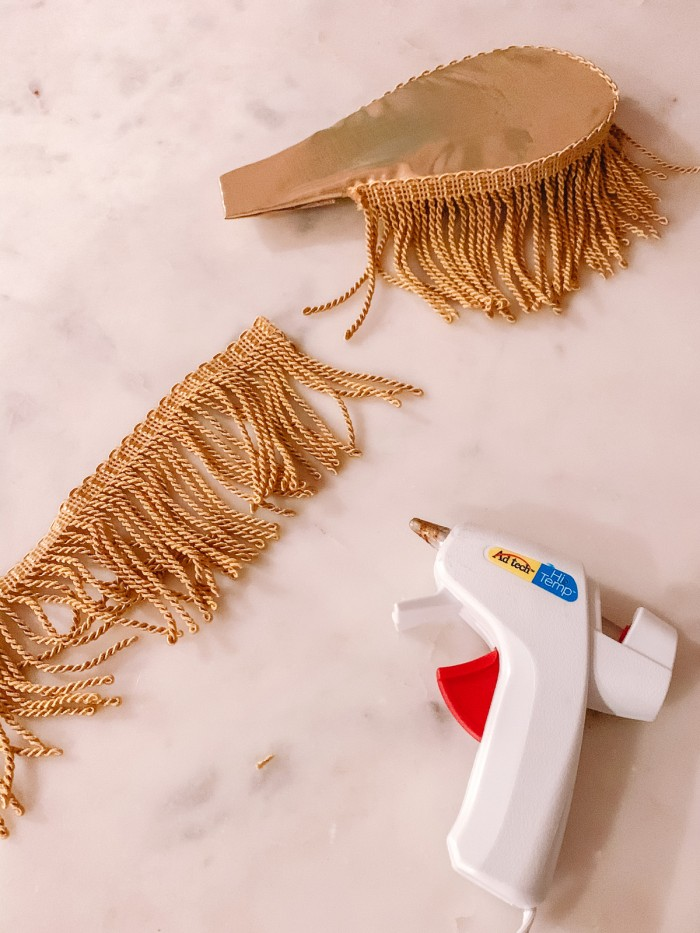Gold fringe on gold epaulettes with a note glue gun on marble table