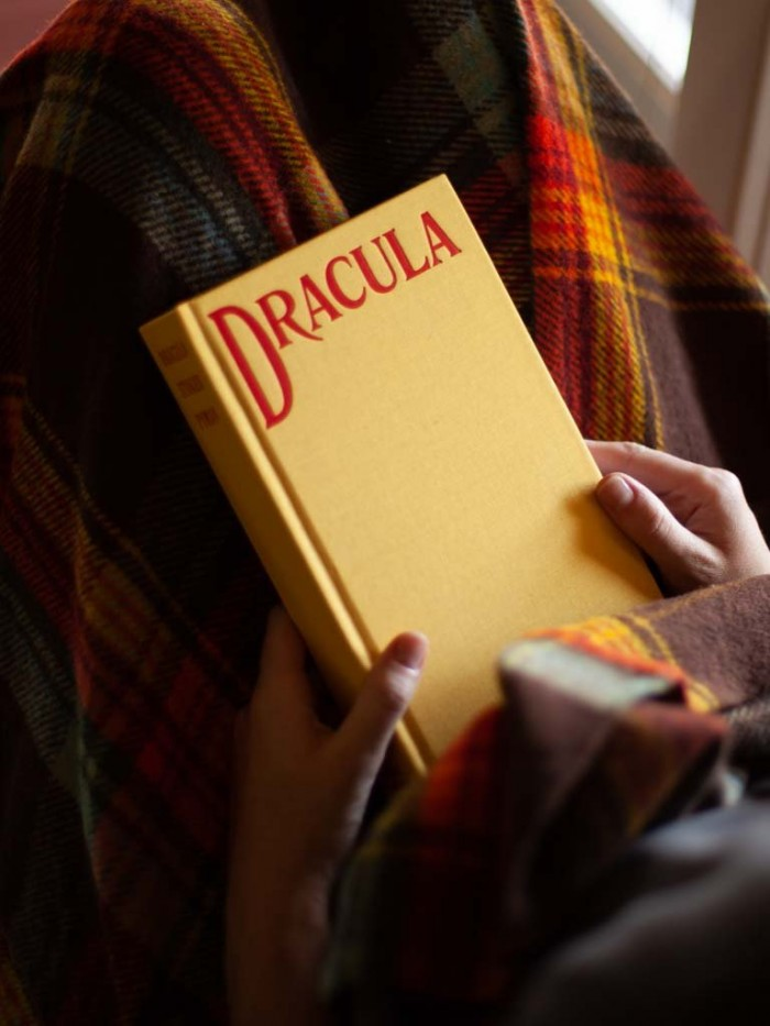 Hands holding Yellow Dracula book over a plaid blanket