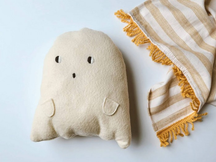 Plush ghost pillow next to a striped blanket on white background