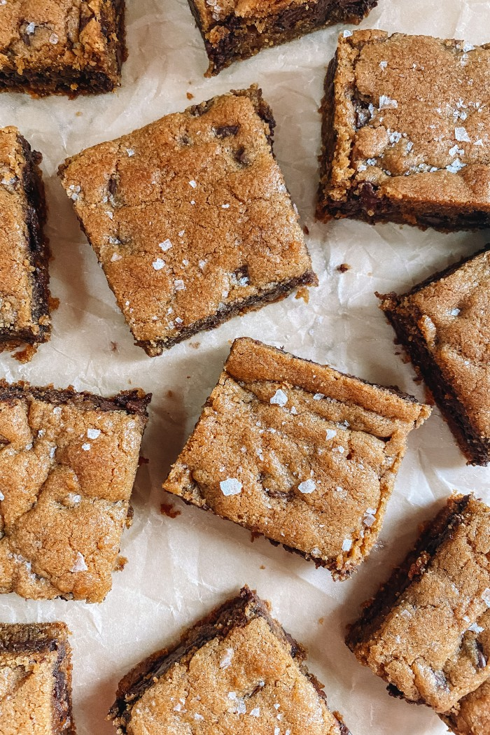 chocolate chip cookie bars on parchment paper with flaked salt on top