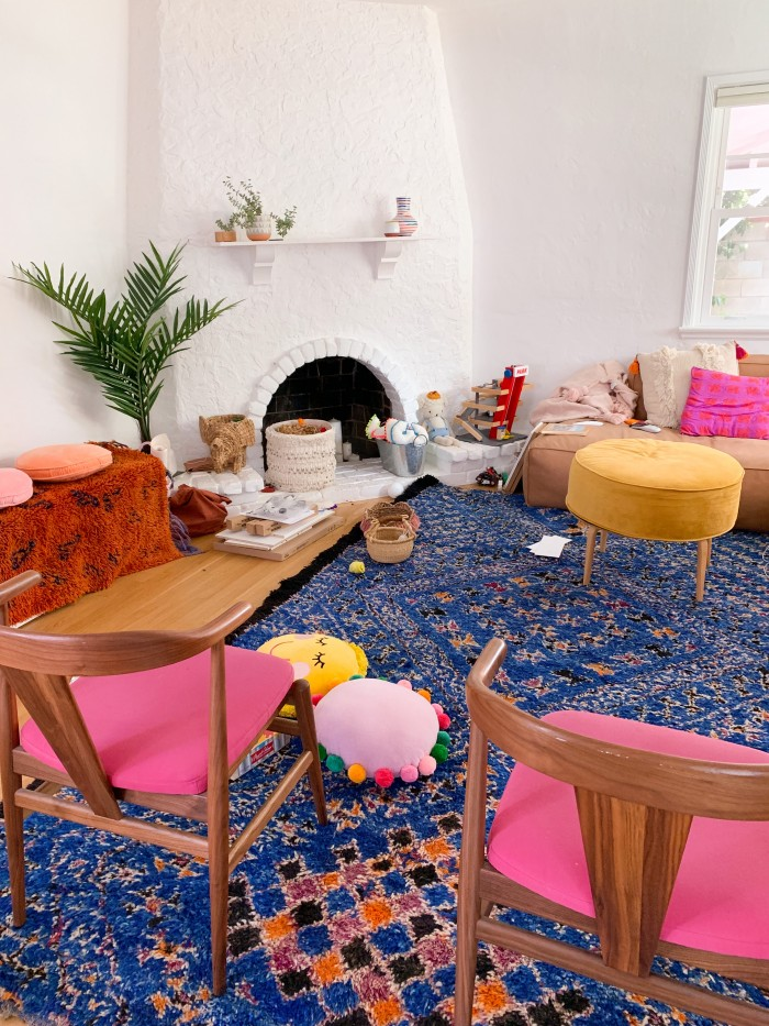 Messy living room with blue rug and pink dining chairs