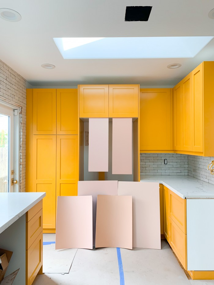 Yellow orange kitchen cabinets with pink paint swatches in front