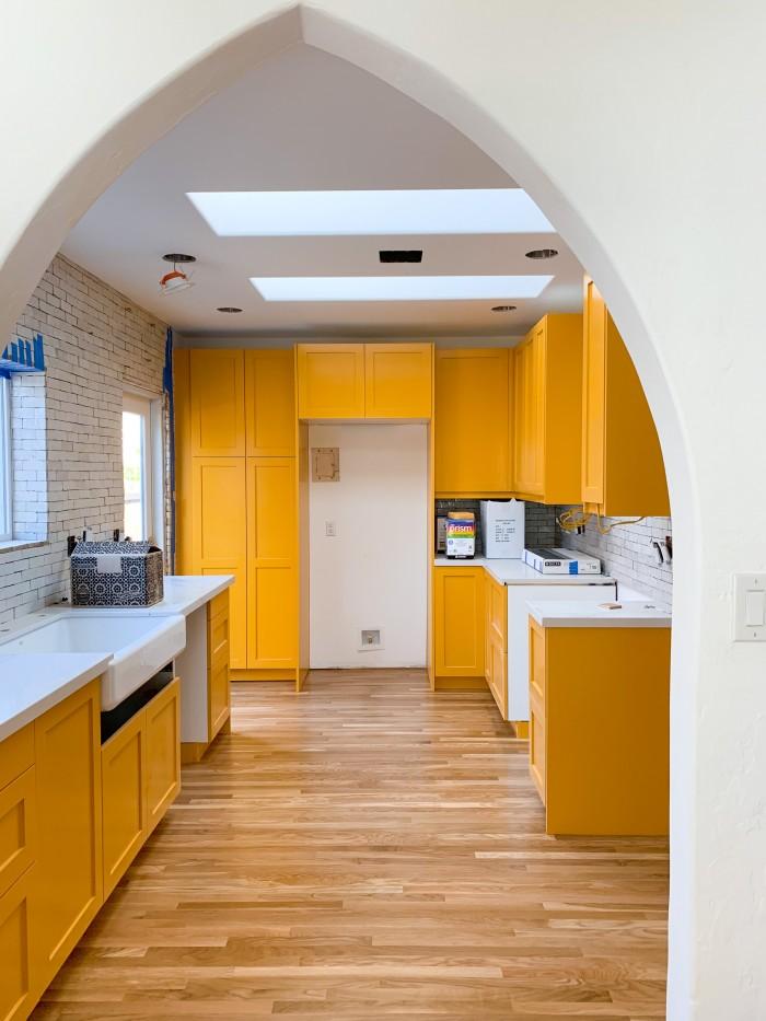 Yellow orange kitchen cabinets with wood floor